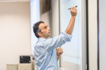 Dr. HaliDr. Halil Bisgin has used his artificial intelligence expertise in collaborations with the FDA and the Beaumont Health System. (Photo by UM-Flint) l Bisgin writAssistant Professor of Computer Science has used his artificial intelligence expertise in collaborations with the FDA and the Beaumont Health System. (Photo by UM-Flint) ing on a whiteboard