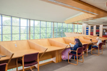 Three students study at desks in UM-Flint's Thompson Library.