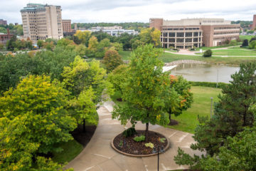 A scene of campus facing the Flint River, White Building, and Northbank Center. The trees are green and the sidewalk is wet as it's just been raining.