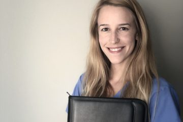Quinn Hanses poses for a portrait. She is wearing blue nursing scrubs and is holding a UM-Flint School of Management padfolio.