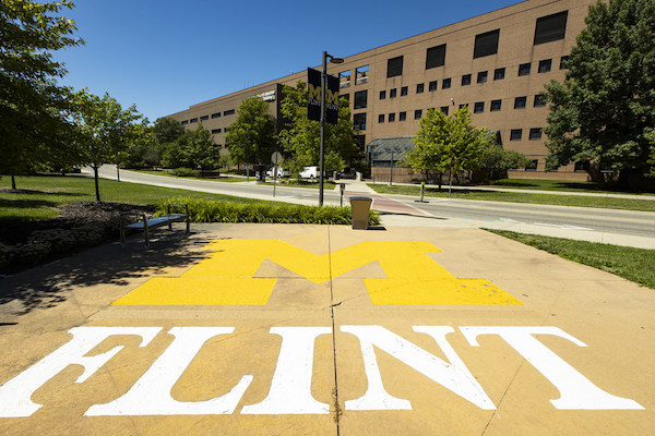 The UM-Flint logo (Block M in yellow with Flint underneath in white) on the sidewalk in front of a building on campus.