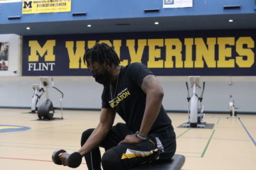 A UM-Flint student lifts a weight on the gym floor of the UM-Flint Rec Center.