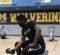 A UM-Flint student lifts a weight on the gym floor of the UM-Flint Rec Center.