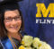 Holly Attebury in graduation regalia in front of a UM-Flint sign