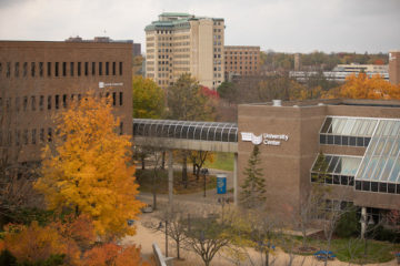 An exterior shot of campus shows the University Center with the Northbank Center in the background. The trees are orange, yellow and red in autumn.