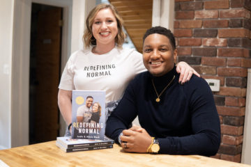 Alexis Lenderman-Black and her husband, Justin Black, pose for a portrait. They sit at a table with a copy of their book, Redefining Normal.