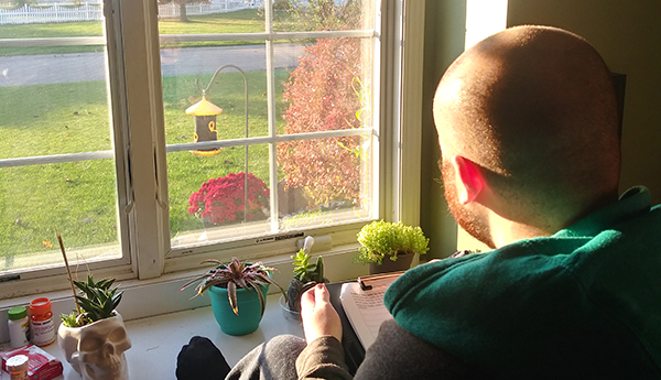 Tyler Lancaster looking out his window to study birds