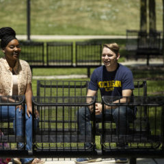 Two UM-Flint students sit and talk on a bench on campus.
