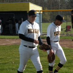 Two male UM-Flint students wearing white baseball uniforms with blue hats and carrying baseball gloves walk out onto a baseball field with a dugout in the background.