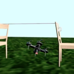 A gray drone flies underneath a rope held up by two chairs as part of an obstacle course.