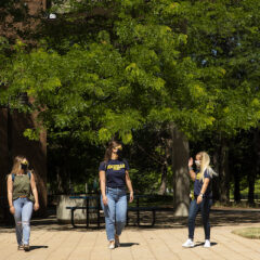 Three female students walk through the UM-Flint campus in the spring
