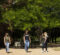 Three female students walk through the UM-Flint campus in the spring