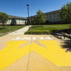 UM-Flint's First Street Residence Hall in the background on a summer day with the Block M logo prominently in front on the sidewalk.