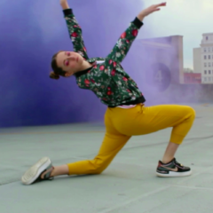 Meredith Sheatzley dancing on a rooftop with colored smoke behind her