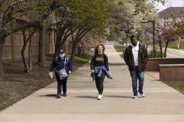 Three UM-Flint students walk along a sidewalk on campus.