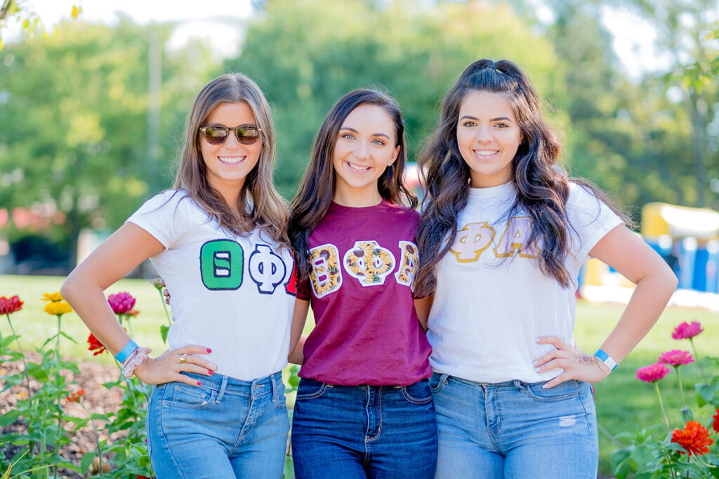 Three female students posing for the camera wearing greek letters.