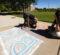 Photo of Alex Grimes drawing non-profit logo with sidewalk chalk