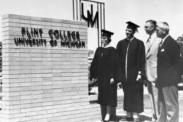Students in graduation apparel standing next to a Flint College sign