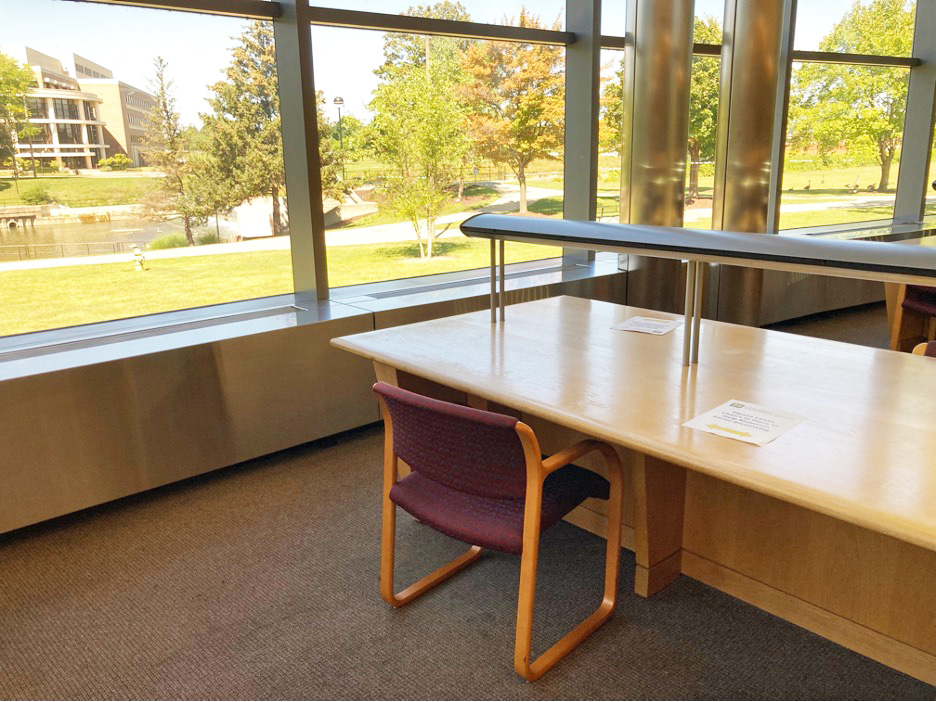 desks next to large windows in the library atrium