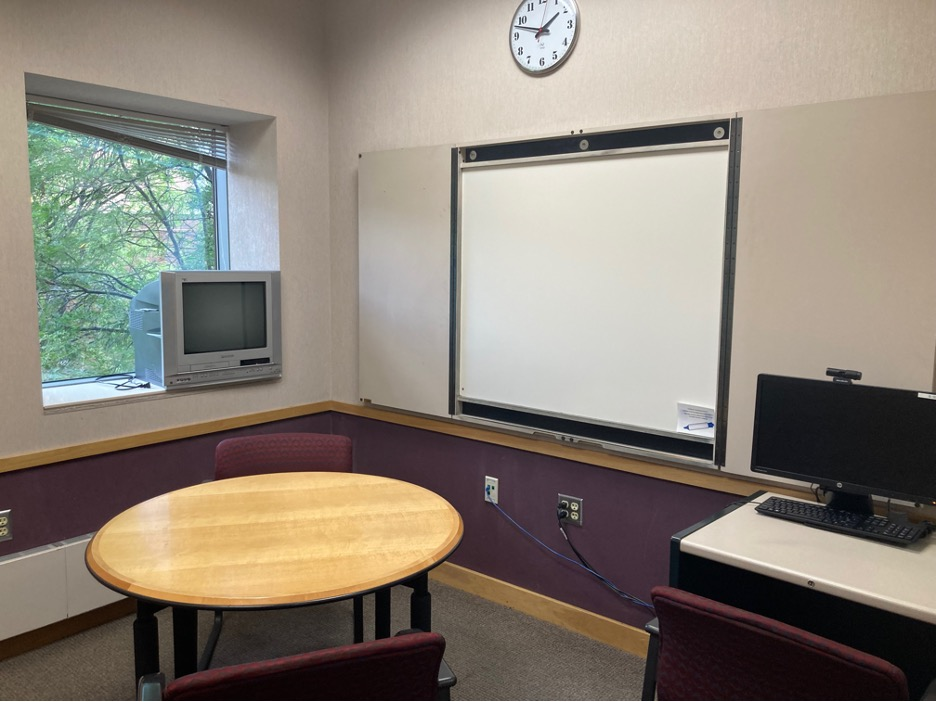 A study room with a whiteboard and tables.