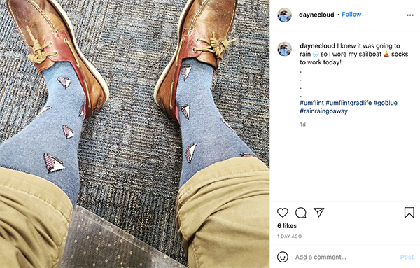 rolled up pants displaying dress socks with sailboats on them.