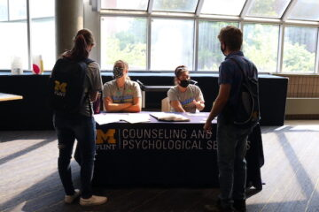 Two UM-Flint students stand at a table and talk to CAPS counselors.