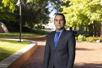 Thiago Ferreira standing outside on campus wearing a suit.
